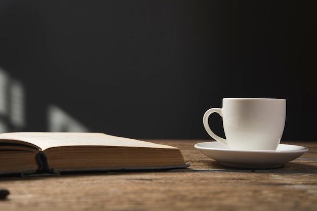 Boek en een kopje koffie op een houten tafel