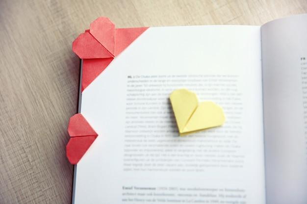 Boek en hartvormige bladwijzer op een lichte houten ondergrond