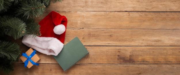 Boek en hoed van de kerstman op een houten achtergrond. bovenaanzicht, plat gelegd. banier.