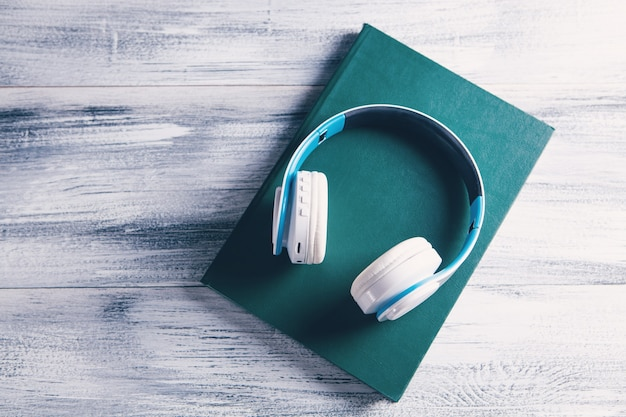 Boek en moderne koptelefoon op lichte ondergrond
