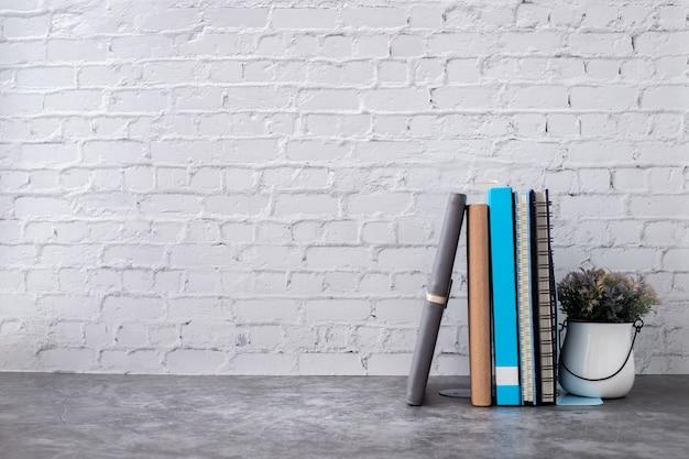 Boek en notitieboekjedocument op bakstenen muur in huis.