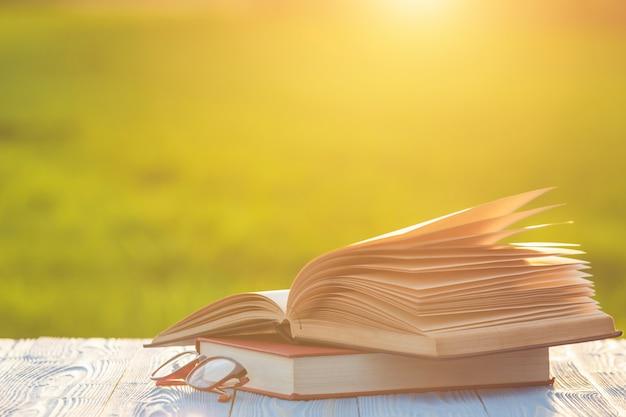 Boek en oogglazen op houten lijst met abstract onduidelijk beeld en bokeh in zonsopgang of zonsondergangtijd