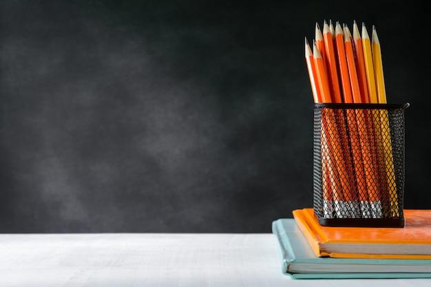 Boek en potlood op witte tafel zwarte bord achtergrond met studie en onderwijs