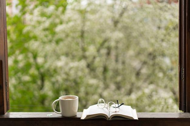 Boek, glazen, kopje thee en rode tulpen op een houten raam
