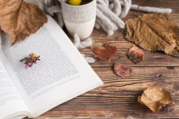 Boek in de buurt van citroenthee en herfstbladeren