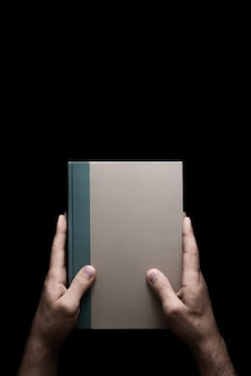 Boek in mannelijke handen op een zwarte achtergrond 1 van 7