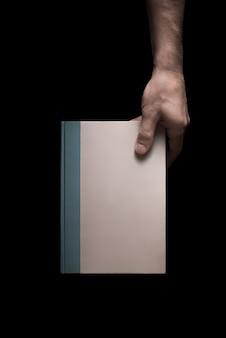 Boek in mannelijke handen op een zwarte achtergrond 3 van 7