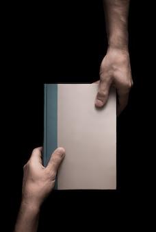 Boek in mannelijke handen op een zwarte achtergrond 5 van 6