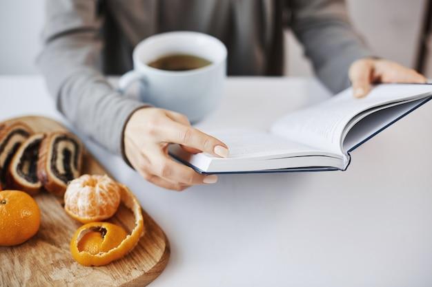 Boek is als een kenniskamer. slimme moderne vrouw leest favoriete roman tijdens het ontbijt, geniet van het drinken van hete thee in een rustige en gezellige sfeer, schilt mandarijn en eet