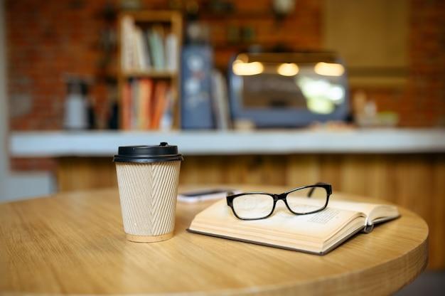 Boek, kopje koffie en glazen op de tafel in studentencafé geopend. een onderwerp leren in het koffiehuis, het onderwijs en het voedselconcept. campuscafetaria, niemand