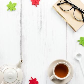 Boek, kopje thee, theepot, snoep en glazen, plat liggen. gezellige achtergrond, concept lezen. kopieer ruimte