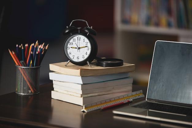Boek, laptop, potlood, klok op houten tafel in bibliotheek, onderwijs leren concept