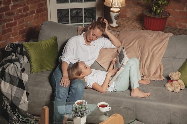 Boek lezen. moeder en dochter tijdens zelfisolatie thuis terwijl ze in quarantaine zijn, familietijd gezellig en comfortabel, huiselijk leven. vrolijke en gelukkig lachende modellen. veiligheid, preventie, liefdesconcept.