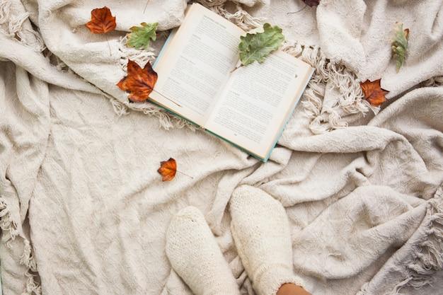 Boek ligt op een beige wol plaid. herfst gevallen bladeren en poten met gebreide witte wollen sokken