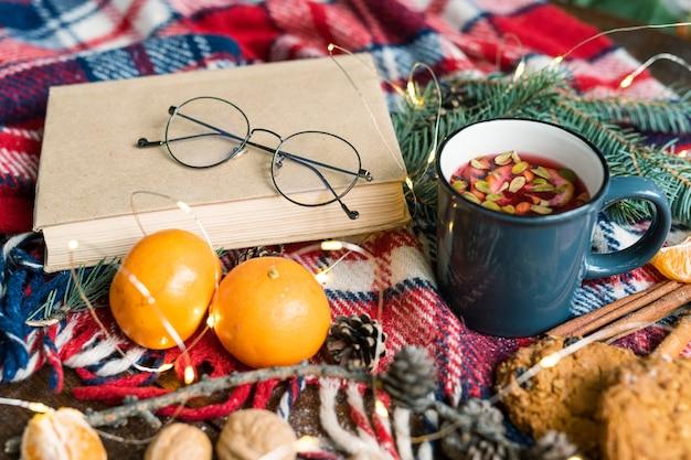 Boek met bril, mok hete kruidenthee, twee mandarijnen, kegels en koekjes op warme sjaal
