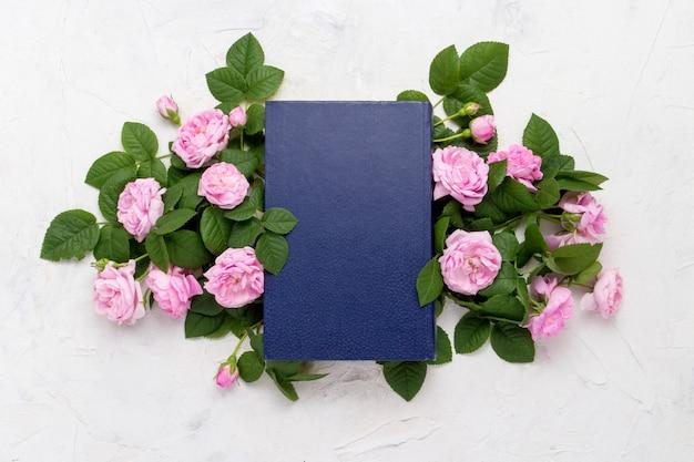 Boek met een blauwe kaft en roze rozen op een lichte stenen achtergrond. plat lag, bovenaanzicht