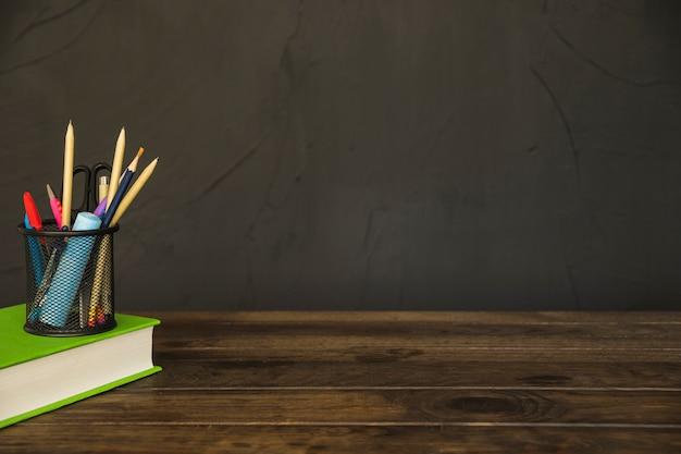 Boek met potloodbeker met kantoorbehoeften op bureau