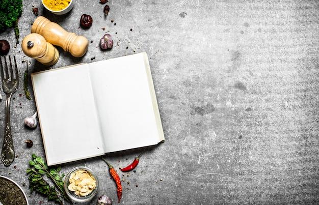 Boek met recepten. verse kruiden en specerijen. op een stenen achtergrond.