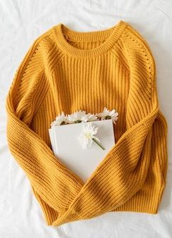 Boek met witte chrysantenbloemen aan de binnenkant en een gele trui op een witte stoffenachtergrond