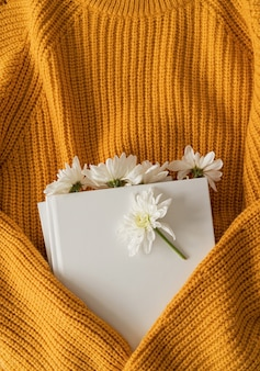 Boek met witte chrysantenbloemen erin en een gele trui van dichtbij