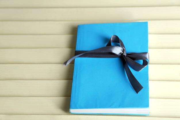Boek omwikkeld met kleurenlint, op houten ondergrond