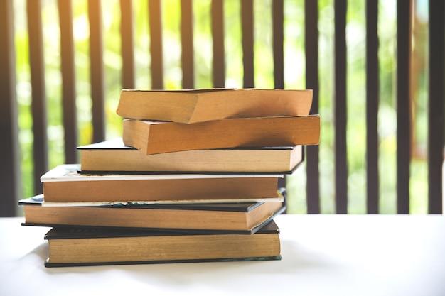 Boek op bureau in de bibliotheekruimte dichtbij venster met vage nadruk voor achtergrond, onderwijs