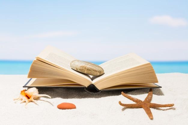 Boek op het strand met wit zand