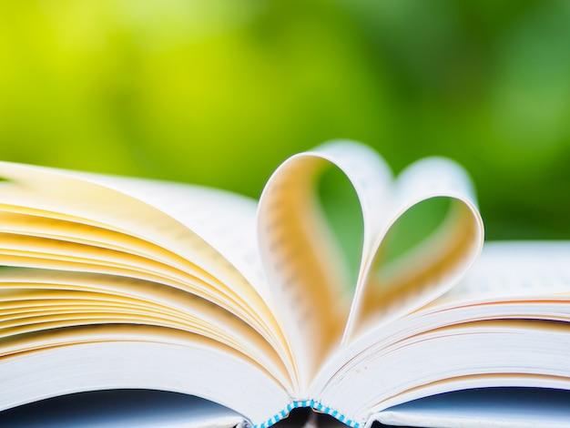 Boek op tafel in de tuin met de bovenste geopende en vormende hartvorm