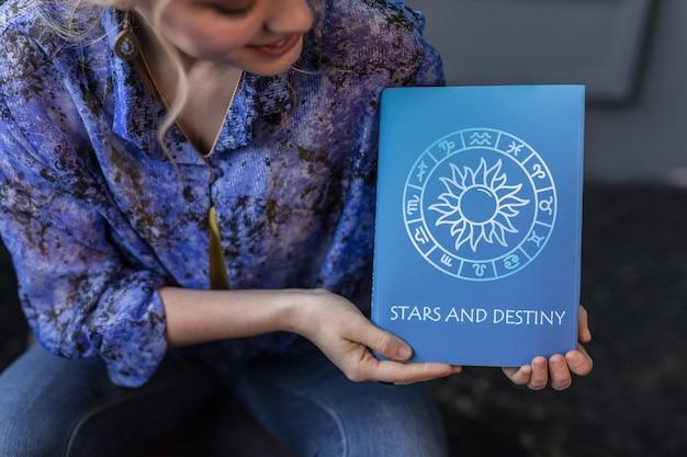 Boek over astrologie. bovenaanzicht van een astrologisch boek dat in vrouwelijke handen is terwijl het aan jou wordt getoond