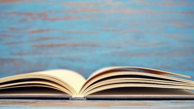 Boek over blauwe houten achtergrond.