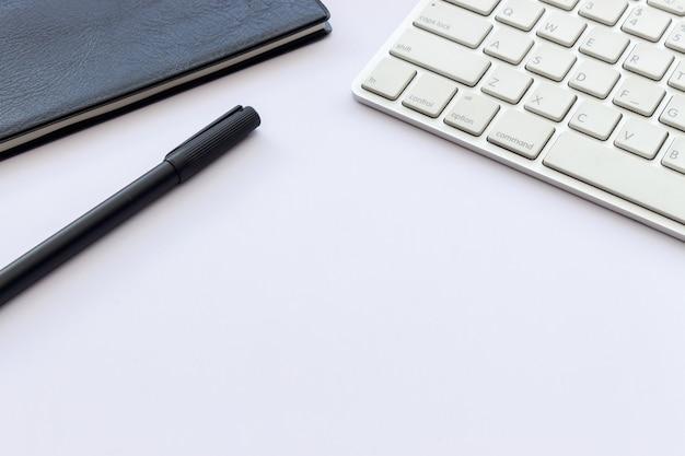 Boek, pen en computertoetsenbord op witte lijst met over licht