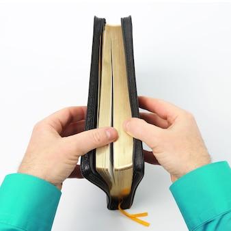 Boek van de bijbel in de handen op witte achtergrond