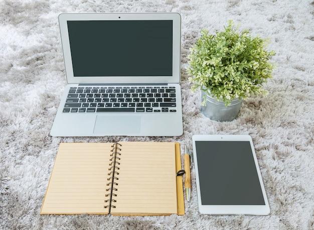 Boek van de close-up het bruine nota, bruine pen, computernotitieboekje, tablet en kunstmatige installatie op grijze stoffen capet geweven achtergrond