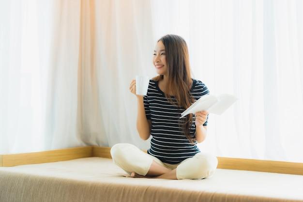 Boek van de de vrouwenlezing van het portret de mooie jonge aziatische en greepkoffiekop of mok binnen op bank op woonkamergebied