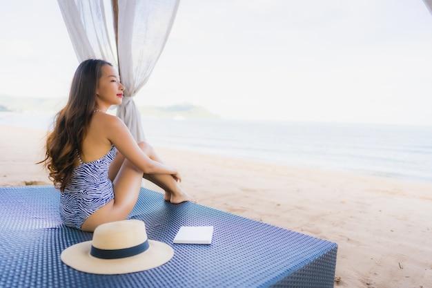 Boek van de de vrouwenlezing van het portret leest het mooie jonge aziatische met gelukkige glimlach in zitkamerbedstoel op de strand overzeese oceaan voor vrije tijd