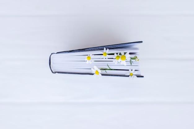 Boek versierd met witte margrietbloemen