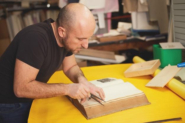 Boekbinder herstelt oud boek in ambachtelijke werkplaats