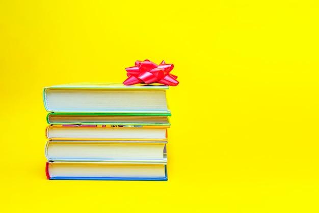 Boeken als cadeau. boeken met een geschenkstrik zijn gestapeld op een gele achtergrond. plaats voor tekst, banner om af te drukken, briefkaartontwerp.