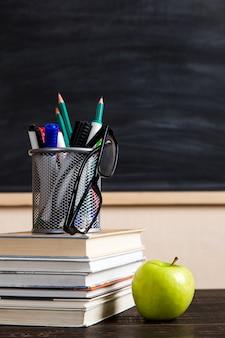 Boeken, appel, pennen, potloden en glazen op een houten tafel, tegen een krijtbord.