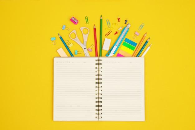 Boeken bedekt met verschillende kleurenapparaten die worden gebruikt bij documentwerk. versier ze om mooi en modern te zijn op een gele achtergrond.