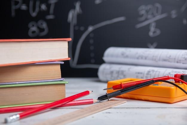 Boeken, digitale multimeter, liniaal en potloden op bord. onderwijs concept.
