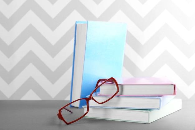 Boeken en bril op grijze tafel tegen ornamentmuur
