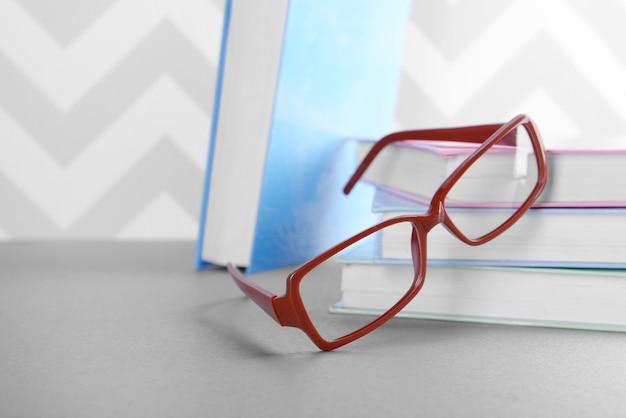 Boeken en brillen op grijze tafel tegen ornamentmuur, close-up