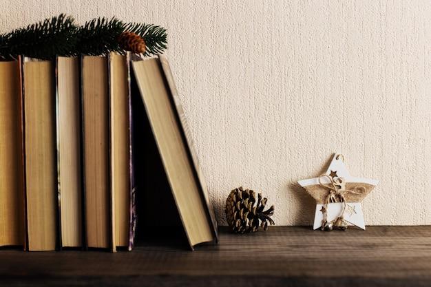 Boeken en een kerstboom met kegels en een sterdecoratie op een oude houten plank.