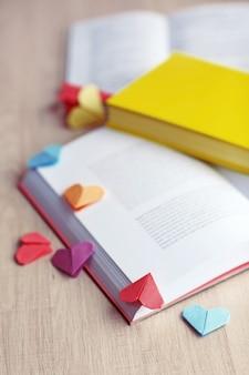 Boeken en hartvormige bladwijzers op een lichte houten achtergrond