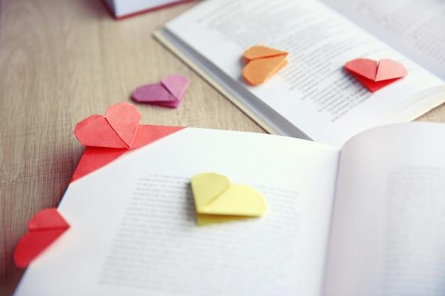 Boeken en hartvormige bladwijzers op een lichte houten ondergrond
