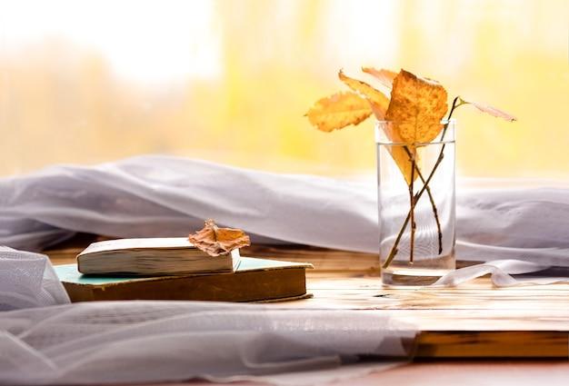 Boeken en herfstbladeren op de achtergrond van het raam, zijaanzicht - het concept van een gezellig tijdverdrijf voor een goed boek op herfstdagen.