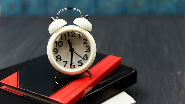 Boeken en klok alarm horloge wit op een houten blauwe achtergrond