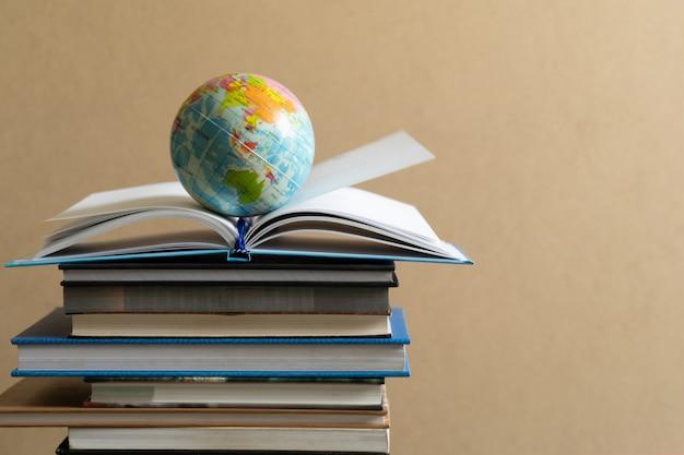 Boeken en leerboek op houten bureau in bibliotheek.