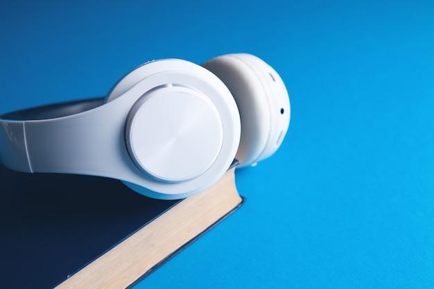 Boeken en moderne koptelefoon op lichtblauwe ondergrond